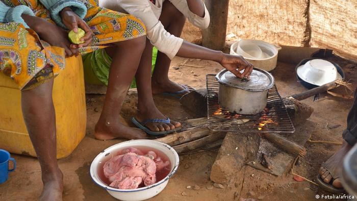 Women cook over a fire in Africa