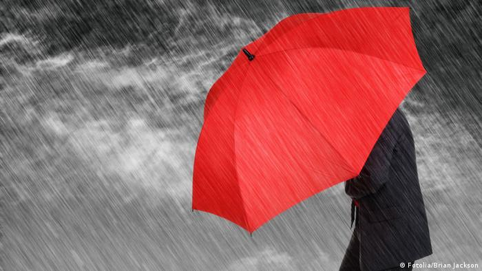 Ein Mann im Anzug wehrt sich mit einem knallroten Schirm gegen peitschenden Regen
