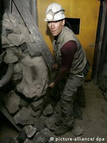 Ein Schauspieler als Bergmann mit Helm und Grubenleuchte in einem engen abgeschlossenen Raum unter Tage. Er versucht mit seinen Händen rollende Steine aufzuhalten.