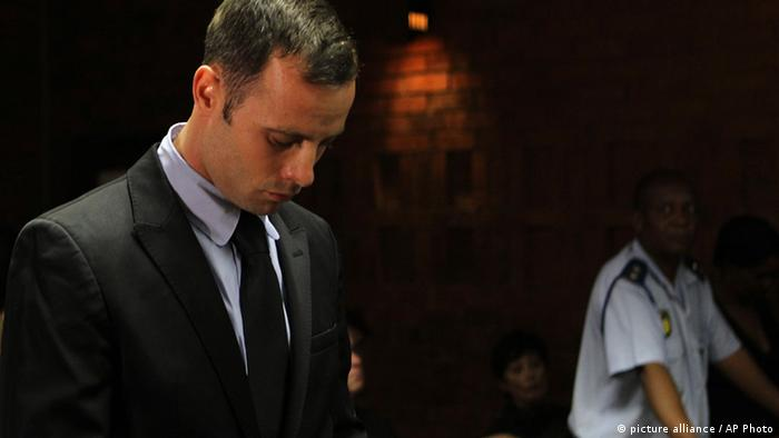 Olympic athlete Oscar Pistorius stands inside the court as a police officer looks on during his bail hearing at the magistrate court in Pretoria, South Africa, Wednesday, Feb. 20, 2013. (Photo: AP/Themba Hadebe)