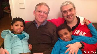Two caucasian men hold their adopted children, both darker skinned, while sitting on a sofa in a residential home
