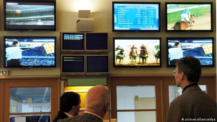 Männer vor Bildschirmen, auf denen Pferderennen, Sportübertragungen und Ergebnisse zu sehen sind.