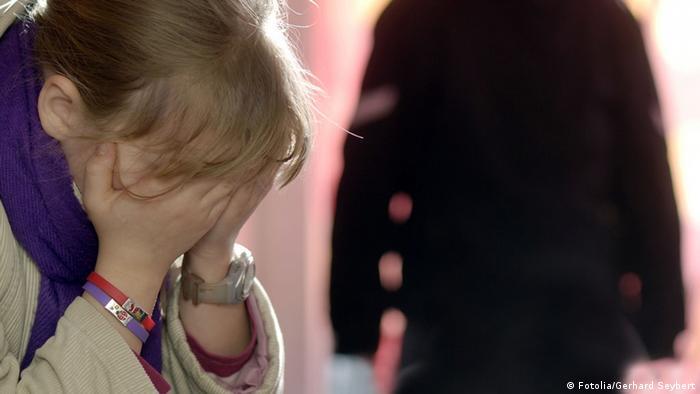 Маленькая девочка закрывает лицо руками
