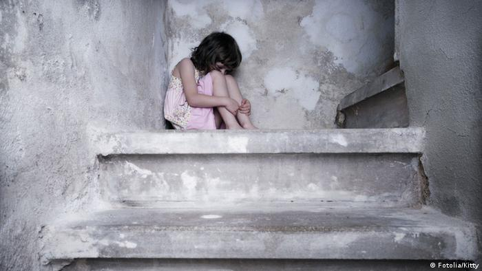 Image to symbolize fear, child abuse. A girl sitting at the top of a set of stairs, knees pulled up tight to cover her face