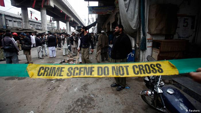 Police investigators cordon off a site of a bomb attack in a market selling mobile phones at Hashtnagri bazaar in Peshawar February 21, 2013. (Photo: REUTERS/Fayaz Aziz)