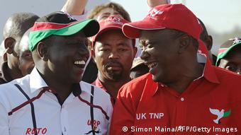 Kenya's Deputy Prime Minister Uhuru Kenyatta (R), who is also the Jubilee Alliance Presidential candidate, speaks with his running mate William Ruto on February 13 ,2013 before addresses supporters during a political rally in the capital Nairobi, ahead of next month's general election. AFP PHOTO/ SIMON MAINA (Photo credit should read SIMON MAINA/AFP/Getty Images)