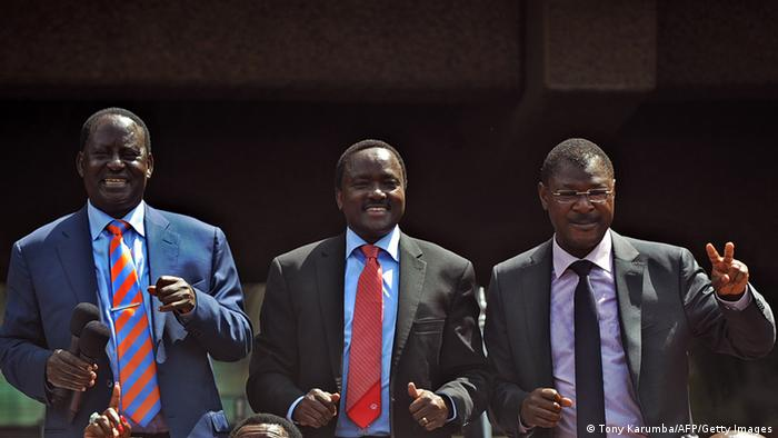 Kenyan Prime Minister Raila Odinga (L), Vice President Kalonzo Musyoka (C) and Trade Minister Moses Wetangula gesture at supporters in Nairobi on December 4, 2012 after agreeing to form a powerful alliance as running mates in presidential elections due in March 2013. The former rivals along with leaders of 10 other smaller parties, signed an agreement in front of thousands of supporters to form the Coalition for Reform and Democracy (CORD) party. Odinga is widely tipped to be the presidential candidate with Musyoka as his deputy, although no formal announcement was made. AFP PHOTO / TONY KARUMBA (Photo credit should read TONY KARUMBA/AFP/Getty Images)