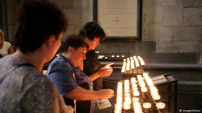 Frauen zünden Kerzen an während in einer Kirche (Foto: Imago/Ulmer)
