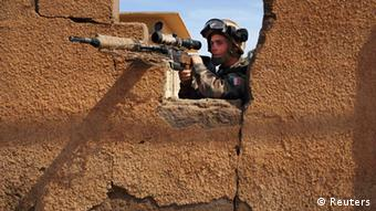 A French solder aims his gun from behind a wall, French soldiers have intervened in various African conflicts, including Mali