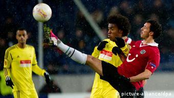 Hannovers Sergio Da Silva Pinto (r.) kommt mit seinem gestreckten Bein vor Willian an den Ball. Foto: Sebastian Kahnert/dpa