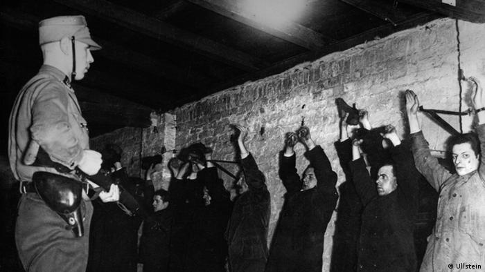 Штурмовик СА держит под прицелом арестованных