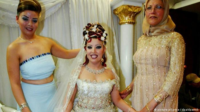 Tunesian bride in a white dress, or Kiswa stands between her mother and a bridesmaid. (Photo: Mike Nelson dpa)