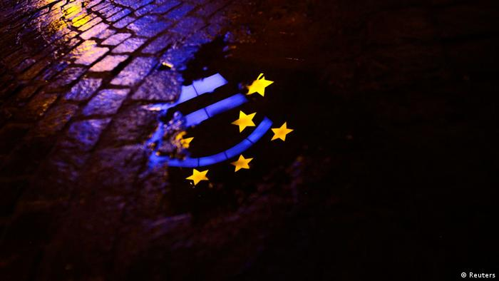 File picture shows the Euro sculpture partially reflected in a puddle on a cobblestone pavement in front of the headquarters of the European Central Bank (ECB) in Frankfurt January 21, 2012. A bumper return of 3-year loans to the ECB would boost the case for it exiting crisis mode, a top Bundesbank official said ahead of February 22, 2013 news on how much banks will hand back at a repayment window next week. The ECB lent banks a total of more than 1 trillion euros ($1.32 trillion) in twin 3-year, ultra-cheap lending operations in December 2011 and February 2012 - a ploy that ECB President Mario Draghi said avoided a major, major credit crunch. Picture taken January 21, 2012. REUTERS/Kai Pfaffenbach/File (POLITICS BUSINESS)