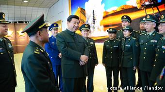 LANZHOU, Feb. 6, 2013 (Xinhua) -- Xi Jinping (C), general secretary of the Communist Party of China (CPC) Central Committee and chairman of the CPC Central Military Commission (CMC), talks with technical personnel and army members at the Jiuquan Satellite Launch Center on Feb. 2, 2013. Xi Jinping visited troops stationed in the nation's northwest ahead of the lunar new year, extending festival greetings and stressing frugality in the army. (Xinhua/Li Gang) (lmm) XINHUA /LANDOV