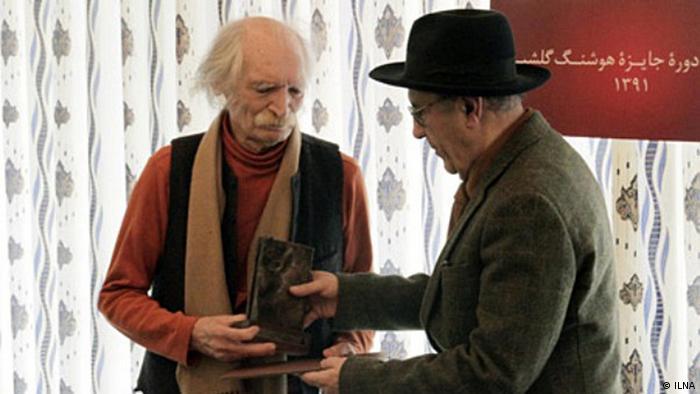 محمود دولتآبادی (راست) در حال دریافت جایزه گلشیری از دست جواد مجابی