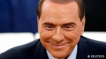 Former Prime Minister Silvio Berlusconi smiles before casting his vote at the polling station in Milan, February 24, 2013. Italians began voting on Sunday in one of the most closely watched elections in years, with markets nervous about whether it can produce a strong government to pull Italy out of recession and help resolve the euro zone debt crisis. REUTERS/Stefano Rellandini (ITALY - Tags: POLITICS ELECTIONS BUSINESS HEADSHOT)