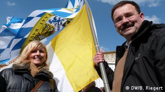 A blonde woman stands next to a man who is holding a yellow flag. (Photo: Bernd Riegert DW)
