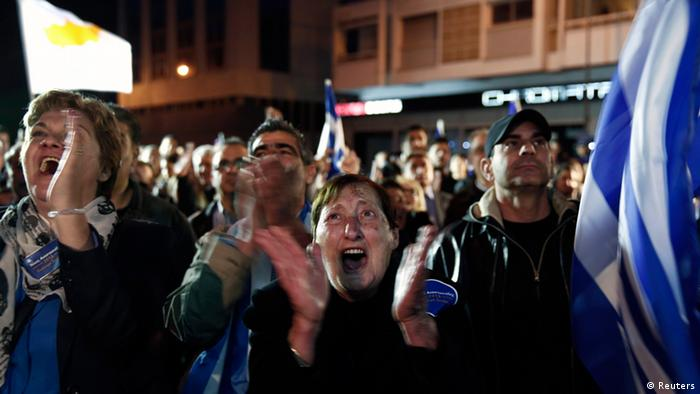 Supporters of conservative Cyprus Presidential candidate Nicos Anastasiades celebrate outside a pre-election campaign bureau in Nicosia February 24, 2013. Anastasiades has sealed a convincing victory in Sunday's presidential run-off vote, according to early results, in a boost for investor hopes of a swift financial rescue for the near-bankrupt nation. Anastasiades, who favours hammering out a quick deal with foreign lenders, took 58 percent of the vote after 30 percent of the vote was counted, well ahead of Communist-backed rival Stavros Malas, who has attacked the austerity terms accompanying a rescue. REUTERS/Yorgos Karahalis (CYPRUS - Tags: POLITICS ELECTIONS)