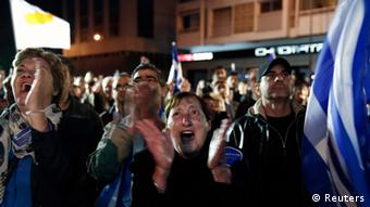 On a darkened plaza, hundreds of supporters clap their hands and wave flags (Photo: REUTERS/Yorgos Karahalis