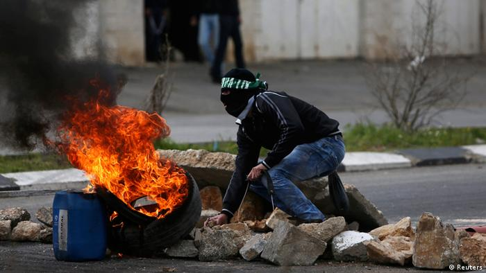 A stone-throwing Palestinian protester crouches near burning tyres during clashes with Israeli soldiers and border policemen outside Israel's Ofer military prison near the West Bank city of Ramallah February 24, 2013. Israel on Sunday demanded the Palestinian Authority stem a surge of anti-Israeli protests ahead of U.S. President Barack Obama's visit to the region next month. The death in an Israeli jail of a Palestinian detainee on Saturday and an on-going hunger strike by four inmates have fuelled tensions in the West Bank. REUTERS/Mohamad Torokman (WEST BANK - Tags: POLITICS CIVIL UNREST)