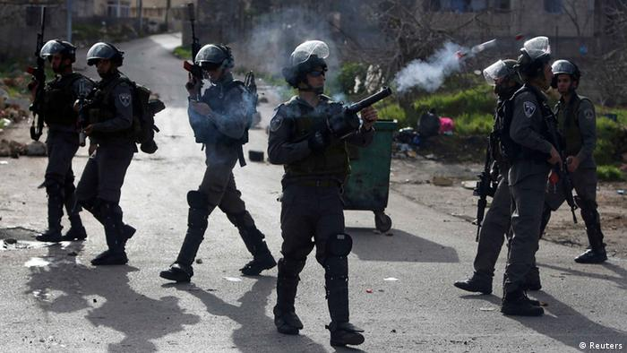An Israeli border policeman fires a tear gas canister during clashes with stone-throwing Palestinian protesters outside Israel's Ofer military prison near the West Bank city of Ramallah February 24, 2013. Israel on Sunday demanded the Palestinian Authority stem a surge of anti-Israeli protests ahead of U.S. President Barack Obama's visit to the region next month. The death in an Israeli jail of a Palestinian detainee on Saturday and an on-going hunger strike by four inmates have fuelled tensions in the West Bank. REUTERS/Mohamad Torokman (WEST BANK - Tags: POLITICS CIVIL UNREST)