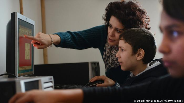 A teacher indicates item on computer screen to boy in Romania
