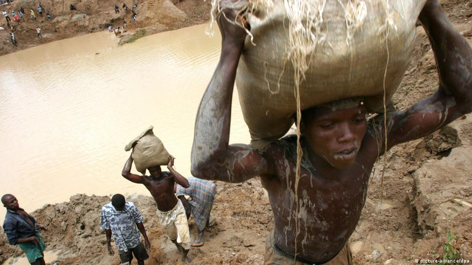 Diamond miners in Sierra Leone carry sacks of gravel out of an open pond