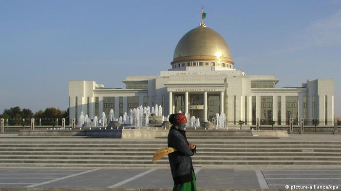 Женщина в маске у президентского дворца в Ашхабаде. Жители Туркмении носили маски еще до пандемии, чтобы защититься от пыли (фото из архива)