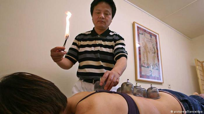 A doctor giving a patient a treatment of Chinese medicine. Photo: Karl-Josef Hildenbrand dpa/lby
