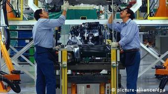Zwei mexikanische Fabrik-Arbeiter bauen einen VW New Beetle zusammen (Foto: picture-alliance/dpa)