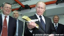 January 24, 2011. Russian Prime Minister Vladimir Putin holding a gold bar while visiting the Central Depository of the Bank of Russia. Georgy Luntovsky (left), first deputy chief of the Central Bank of Russia.
