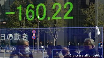 epa03600999 Pedestrians are reflected in a stock market electronic board in Tokyo, Japan, 26 February 2013. Tokyo stocks fell sharply at the morning session by 160.22 points, or 1.37 percent, following Italy's general election results. EPA/FRANCK ROBICHON