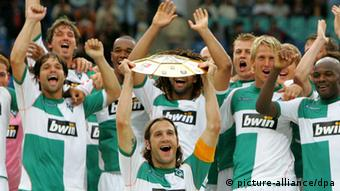 Captain Torsten Frings holds the German League Cup, celebrating with his Werder Bremen team mates.
