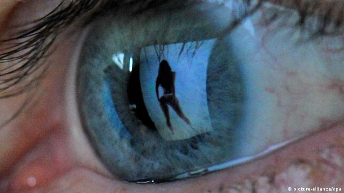 A close up picture of a human eye, reflecting an image of woman dressed in her underwear
