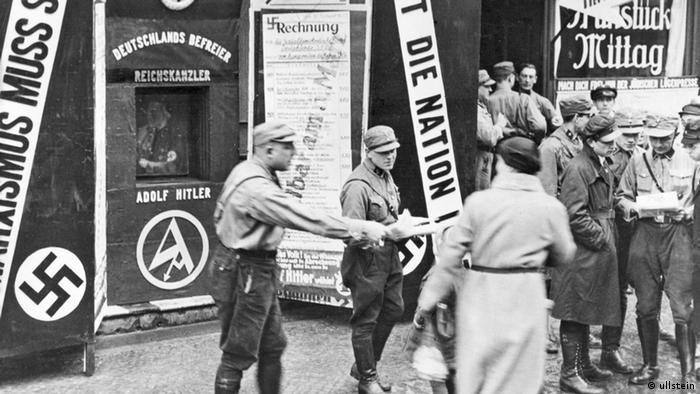 A black-and-white photo shows men in the 1930s handing out voting information (Photo: no info)