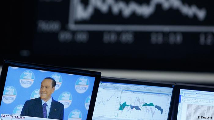A TV screen showing news on Italy's former Prime Minister Silvio Berlusconi is pictured in front of the German share price index DAX board at the German stock exchange in Frankfurt February 26, 2013. REUTERS/Lisi Niesner (GERMANY - Tags: BUSINESS POLITICS)