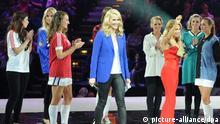 Die Moderatorinnen Judith Rakers (M) und Topmodel Sylvie van der Vaart (3.v.r.) stehen am 29.09.2012 in Hamburg bei der Gala zum 125-jährigen Bestehen des HSV mit Models in alten HSV-Trikots auf der Bühne. Foto: Angelika Warmuth/dpa +++(c) dpa - Bildfunk+++ pixel