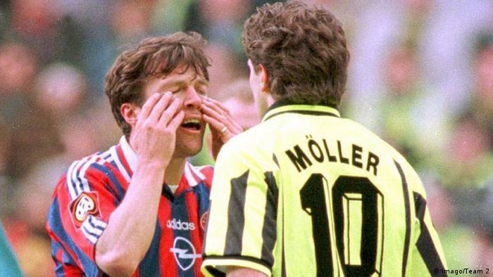 Lothar Matthäus rubs away phanton tears while getting into Andreas Möller's face.