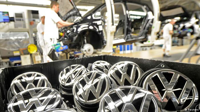 Emblems of VW Golf VII car are pictured in a production line at the plant of German carmaker Volkswagen in Wolfsburg in this February 25, 2013 file photo. Volkswagen said February 27, 2013 it will pay its German workers a 7,200-euro ($9,400) bonus for 2012, a reduction of 4 percent on the previous year's payout despite Europe's biggest car maker having posted a record profit and sales. Picture taken February 25, 2013. REUTERS/Fabian Bimmer/file (GERMANY - Tags: TRANSPORT)