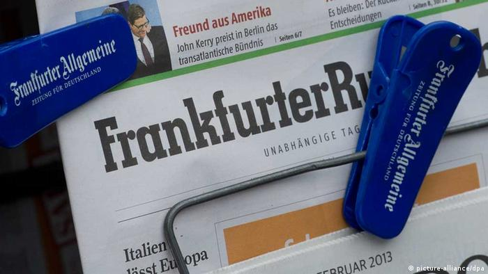 Pegs used by FAZ grasp a copy of the FR at a newspaper stand in Frankfurt on February 27 2013. Photo: Boris Roessler dpa