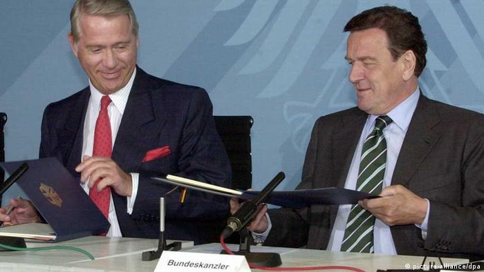 Zwei Männer im Jacket, rechts im Bild Kanzler Schröder, der eine geöffnete Dokumentenmappe zum Energiemanager Hartmann neben ihm reicht, der seine Mappe mit dem Bundesadler halb geschlossen hält