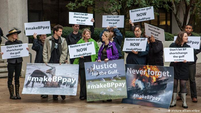 Protesters display placards as the trial against BP stemming from the 2010 explosion of a drilling rig in the Gulf of Mexico began in New Orleans (Photo: EPA/SKIP BOLEN)
