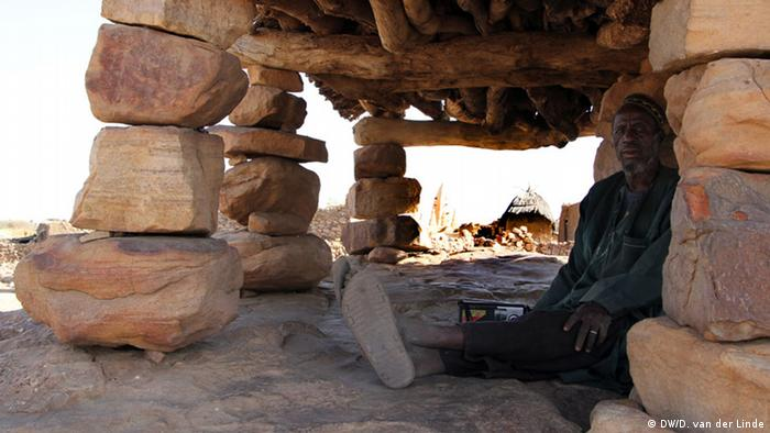 Dourou village elder Yousif Sagara sits underneath the toguna, where leaders meet to discuss every important decision in the community