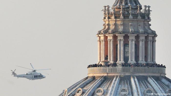 ROME, ITALY - FEBRUARY 28: People crowd the gallery on top of St Peter's Basilica as a helicopter carrying Pope Benedict XVI passes by on its way out of Vatican City on February 28, 2013 in Rome, Italy. (Photo by Peter Macdiarmid/Getty Images)