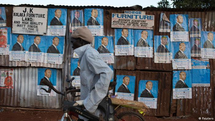 A cyclist moves past campaign posters of Kenya's presidential candidate Peter Kenneth at the Kangemi slum in Kenya's capital Nairobi February 28, 2013. Kenya will hold its presidential and parliamentary elections on March 4. REUTERS/Siegfried Modola (KENYA - Tags: POLITICS ELECTIONS)