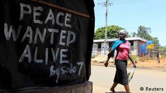 A woman walks past a message of peace in Kibera slum in the capital Nairobi February 28, 2013. Kenya will hold its general elections on March 4. REUTERS/Noor Khamis (KENYA - Tags: ELECTIONS POLITICS)