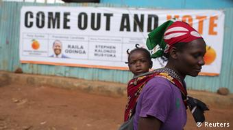 A woman carries her baby as she walks past an Orange Democratic Movement (ODM) campaign poster in Kibera slum in capital Nairobi February 27, 2013. Kenya will hold its presidential and parliamentary elections on March 4. REUTERS/Siegfried Modola (KENYA - Tags: ELECTIONS POLITICS)