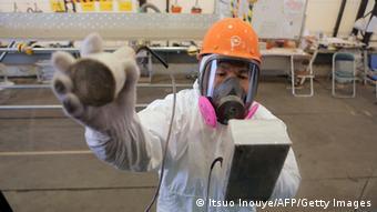 Работник АЭС Фукусима в противогазе проверяет уровень радиации