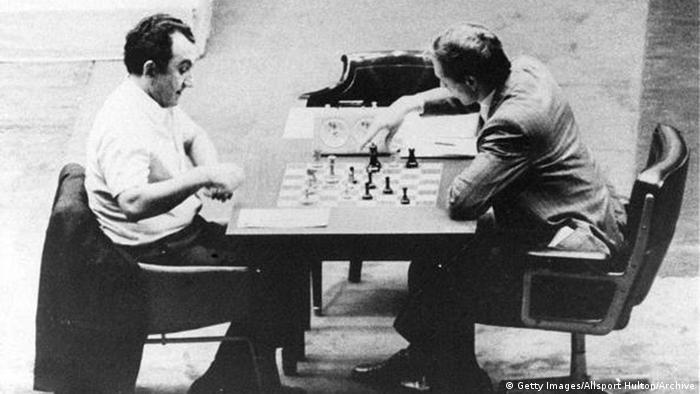 Black and white photo of Tigran Petrosian and Bobby Fischer seated at a table playing chess