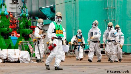 Workers walk near the TEPCO tsunami-crippled Fukushima Daiichi nuclear power plant